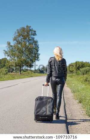 woman dressed in leather clothes walking along the rural roadside - stock photo