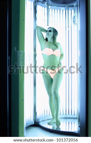 Woman dressed in orange swimsuit and dark glasses stands in solarium; full body - stock photo
