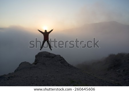 Woman dressed in red is jumping on the rock.  Sunset in mountains. - stock photo
