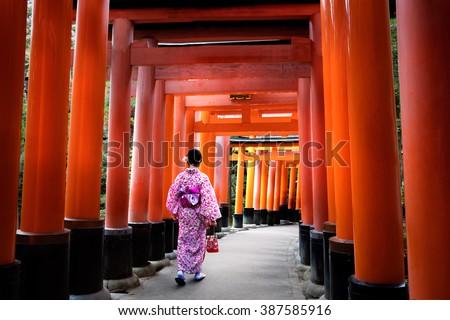Woman dressed in traditional japanese costume walking under tori gates at the fushimi-inari shrine, Kyoto Japan - stock photo