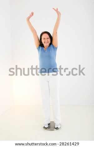 Woman dressed sportswear standing on bathroom scales. She looks very happy. Front view. - stock photo