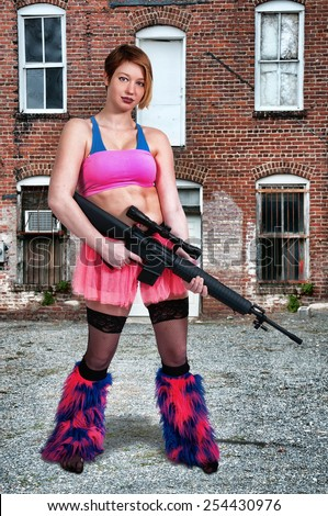 Woman dressed to go to a rave dance party with gun - stock photo