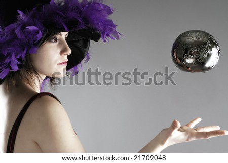 Woman dressed up as a sorceress levitating a silver globe - stock photo