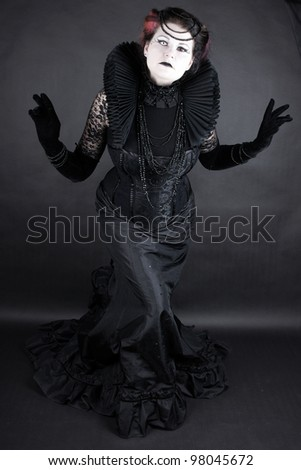 Woman dressed up in gothic style as dark queen in ancient victorian clothing - stock photo