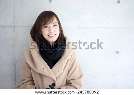 Woman dressed with wool coat and scarf - stock photo