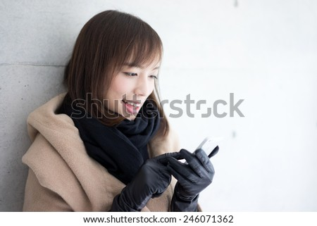Woman dressed with wool coat and scarf using smart phone - stock photo