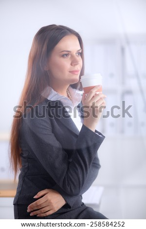 Woman drink coffee at office, standing near desk . - stock photo