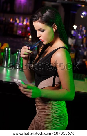 Woman drink in bar and chat by smartphone - stock photo