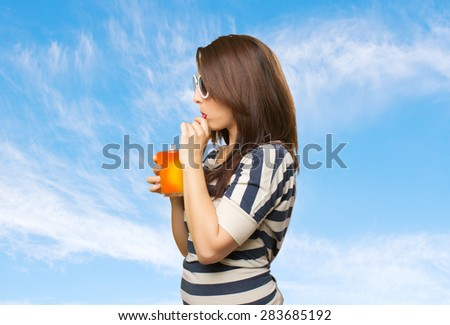 Woman drinking a juice with a red straw. Over clouds background - stock photo