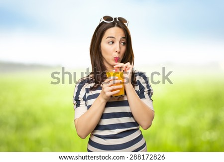 Woman drinking a juice with a red straw. Over nature bokeh background - stock photo
