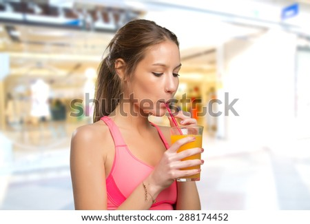 Woman drinking a orange juice with a red straw. Over shopping center background - stock photo