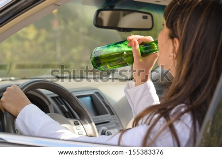 Woman drinking alcohol and driving raising the bottle to her lips to take a swig as she steers the car, view through the side window - stock photo