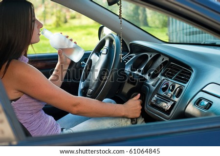 Woman drinking alcohol during a drive in a car