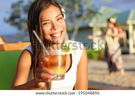 Woman drinking alcohol Mai Tai drink on Hawaii giving toast saying cheers looking at camera at beach club. Beautiful girl enjoying alcoholic beverage cocktail. Smiling happy woman on Hawaiian beach. - stock photo