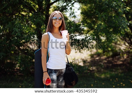Woman drinking at the outdoor water before working out. The girl drinks water - stock photo