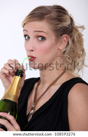 woman drinking champagne through a straw - stock photo