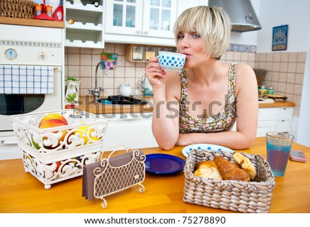 woman drinking coffee and eat breakfast at kitchen table