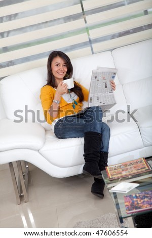 Woman drinking coffee and reading the newspaper - stock photo