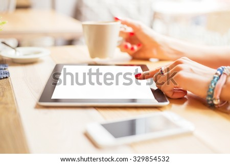 Woman drinking coffee and using tablet  - stock photo
