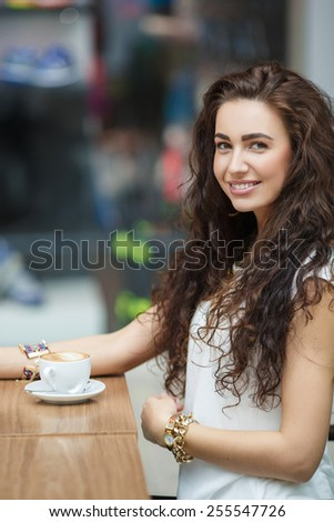 Woman drinking coffee at cafe. Portrait of young beautiful woman sitting in a cafe indoor drinking coffee. Young woman drinking coffee in a trendy cafe - stock photo