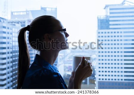 Woman drinking coffee at the office - stock photo