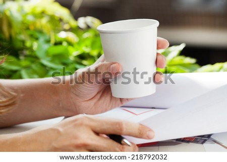 Woman drinking coffee from disposable coffee cup while working. - stock photo