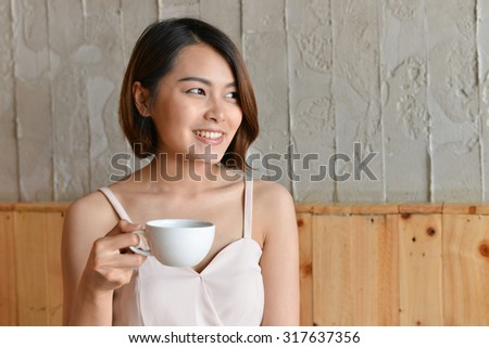 woman drinking coffee in the morning at restaurant (soft focus o - stock photo
