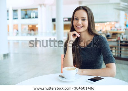 woman drinking coffee in the morning at restaurant soft focus. Smiling pretty girl with cup of tea. Cheerful lady enjoy and relax - stock photo