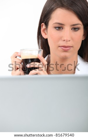 Woman drinking coffee while working at her laptop - stock photo