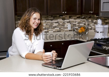 woman drinking coffee while working on the laptop in the kitchen