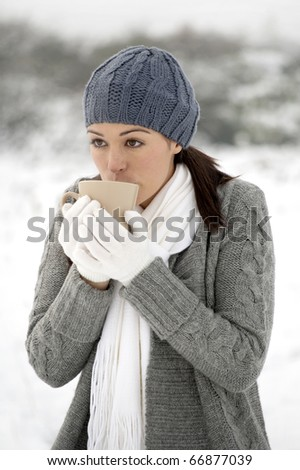 Woman drinking hot drink outside in the snow - stock photo