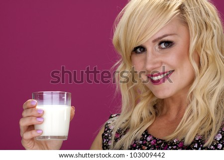 Woman drinking milk. An attractive blond woman drinking a glass of milk. - stock photo