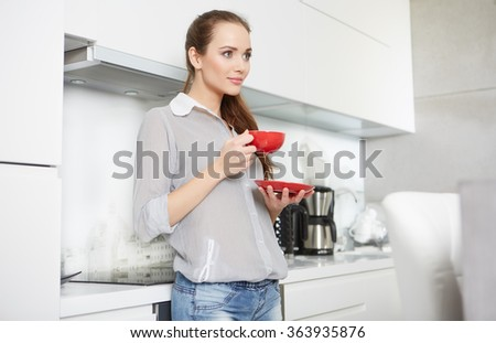 Woman drinking morning coffee in the kitchen - stock photo