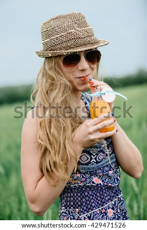 Woman drinking orange juice smiling and posing outdoor. - stock photo