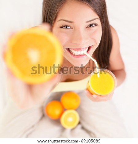 Woman drinking orange juice smiling showing oranges. Young beautiful mixed-race Asian / Caucasian model. - stock photo