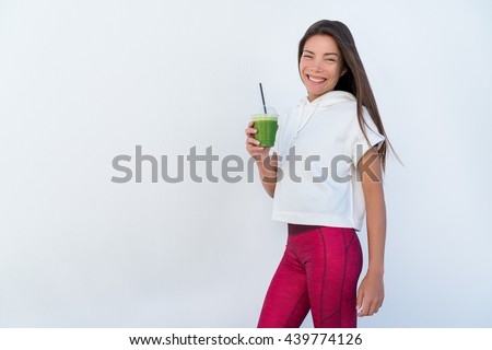Woman drinking vegetable Green detox smoothie after fitness running workout on summer day. Fitness and healthy lifestyle concept with beautiful fit mixed race Asian Caucasian model - stock photo