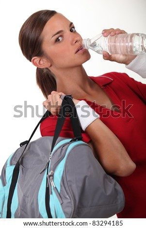 Woman drinking water after a workout - stock photo