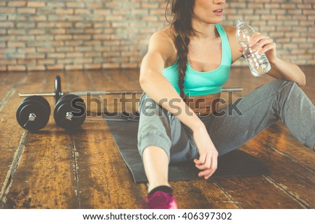 Woman drinking water after training on the sport mat - stock photo