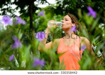 Woman drinking water from bottle during running or workout rest at city park on spring. Female athlete taking a rest for hydration. - stock photo