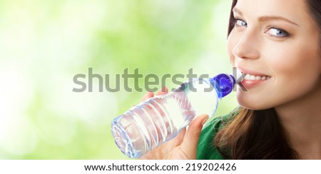 Woman drinking water from bottle, outdoor, with blank area for copyspace - stock photo