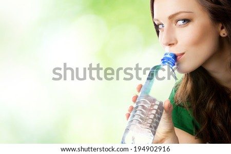 Woman drinking water from bottle, outdoors, with blank area for copyspace - stock photo