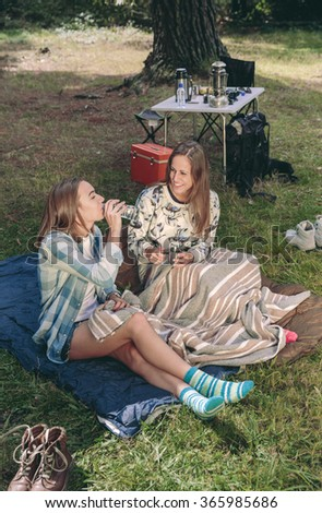 Woman drinking water with friend in campsite - stock photo