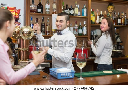 Woman drinking wine at counter and chatting with smiling bartenders. Focus on man