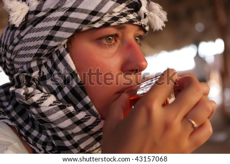 Woman drinks Bedouin tea in Bedouin tent. Excursion in Egypt