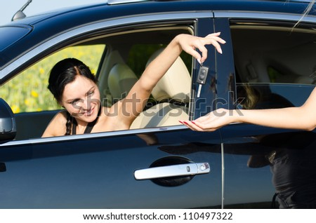 Woman driver handing over her car keys to a second woman standing outside the vehicle