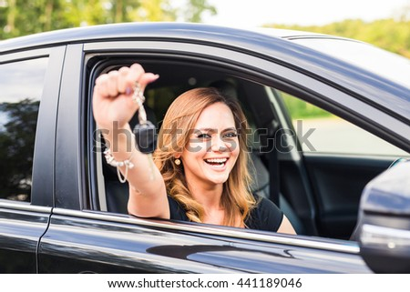 Woman driver holding car keys driving her new automobile Laughing young girl