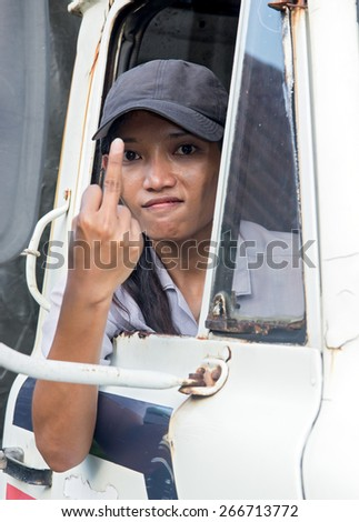 Woman driver of truck showing gesture with her finger.Truck driver shows obscene gesture from car window.Gesture raised finger from truck driver.Aggressive driver shows indecent symbol pointing finger - stock photo