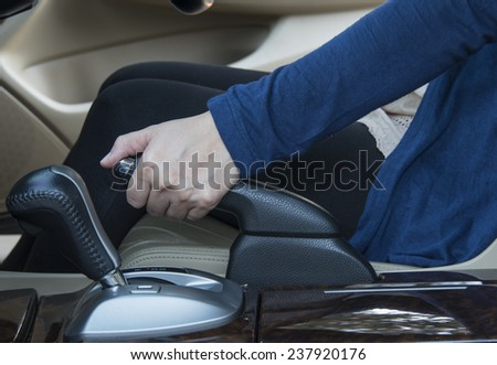 Woman driver pulling the hand brake in car.