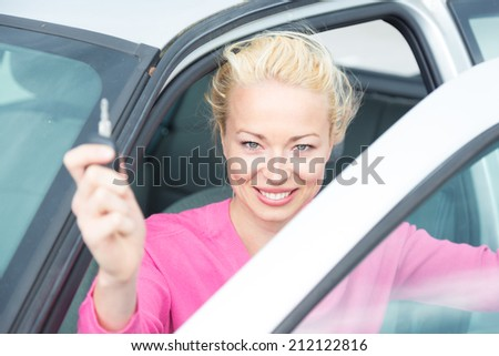 Woman driver showing car keys. Young female driving happy about her new car or drivers license. Caucasian model. - stock photo