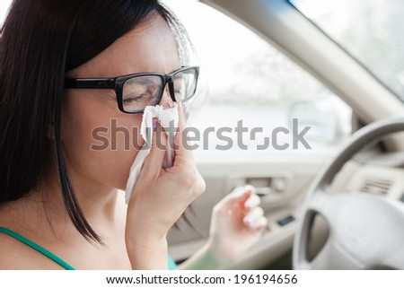 Woman driver sneezing in the car. Sick woman driver. - stock photo